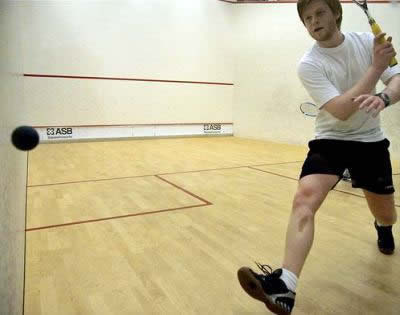 squash rules player hitting a backhand
